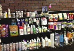 picture of pet supplies on shelf at Primping Pooches in Anchorage Alaska. Products are for pet grooming.